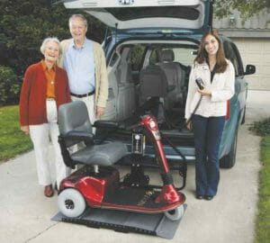 Older couple standing at rear of minivan with lady operating a bruno joey lift with their red scooter on the lift platform.